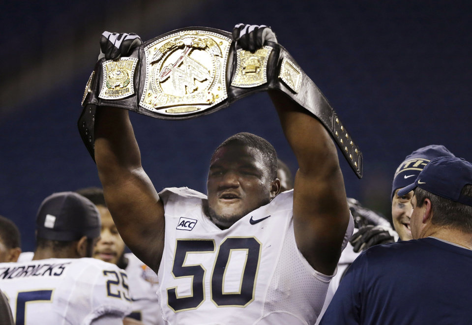 Photo - Pittsburgh defensive lineman Tyrone Ezell holds up a wrestling championship belt after the Panthers defeated Bowling Green 30-27 in the Little Caesars Pizza Bowl NCAA college football game, Thursday, Dec. 26, 2013, in Detroit. (AP Photo/Carlos Osorio)