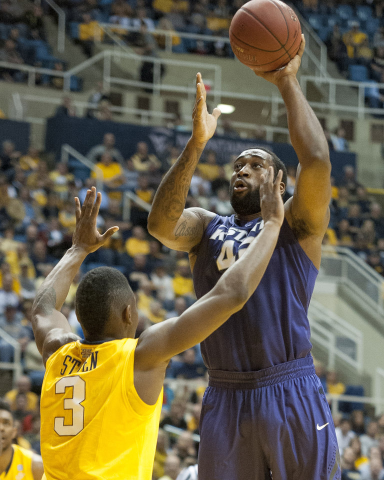 Photo - Kansas State's Thomas Gipson, right, shoots over West Virginia's Juwan Staten during the first half of an NCAA college basketball game Saturday, Feb. 1, 2014, in Morgantown, W.Va. (AP Photo/Andrew Ferguson)