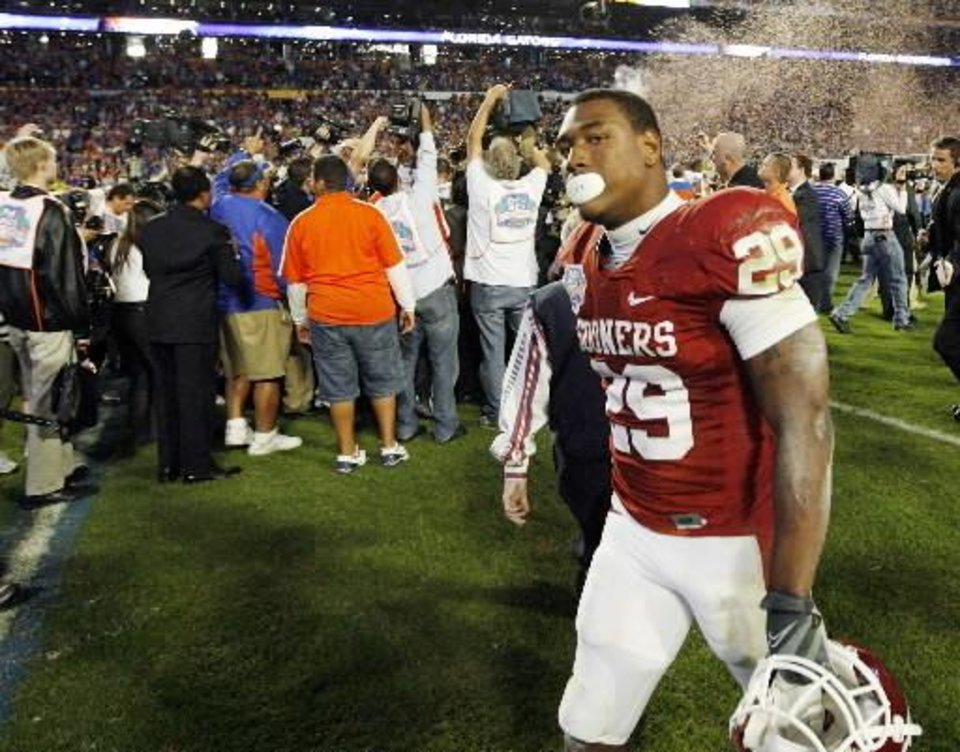 Photo - OU's Chris Brown (29) walks off the field as photographers swarm Florida players after the BCS National Championship college football game. Photo by Nate Billings.