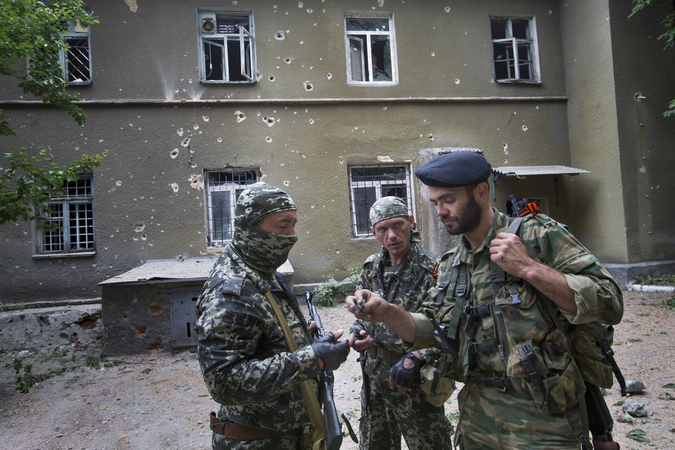 Photo - Pro-Russian armed militants look at pieces of shrapnel at a mental hospital following a motor attack in a fighting between Ukrainian government troops and  insurgents, is seen, Semyonovka village outside Slovyansk, Ukraine, Sunday, May 25, 2014. Ukrainians vote Sunday in an early presidential election that could be a crucial step toward resolving the country's crisis, but separatists in the east are threatening to block the vote. (AP Photo/Alexander Zemlianichenko)