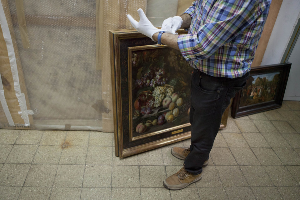 Photo -   Dr. Doron J. Lurie senior curator and chief conservator at the Tel Aviv Museum of Art adjusts his gloves before taking Abraham Breughel's Still Life of Fruit with a Bird, left, and Jan Breughel's Adoration of the Kings paintings into the museum's vault in Tel Aviv, Israel, Monday, Nov. 19, 2012. Tel Aviv's Art Museum, one of Israel's premiere museums, has moved 200 of its most precious works of art to a rocket-proof vault in case of a missile attack. (AP Photo/Dan Balilty)