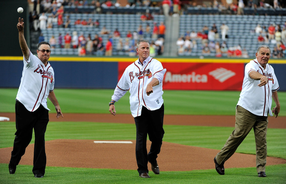 Photo - Hall of Famers Greg Maddux, Tom Glavine and Bobby Cox, from left, throw out the first pitches in unison for a baseball game between the Atlanta Braves and the Washington Nationals, Friday, Aug. 8, 2014, in Atlanta. (AP Photo/David Tulis)