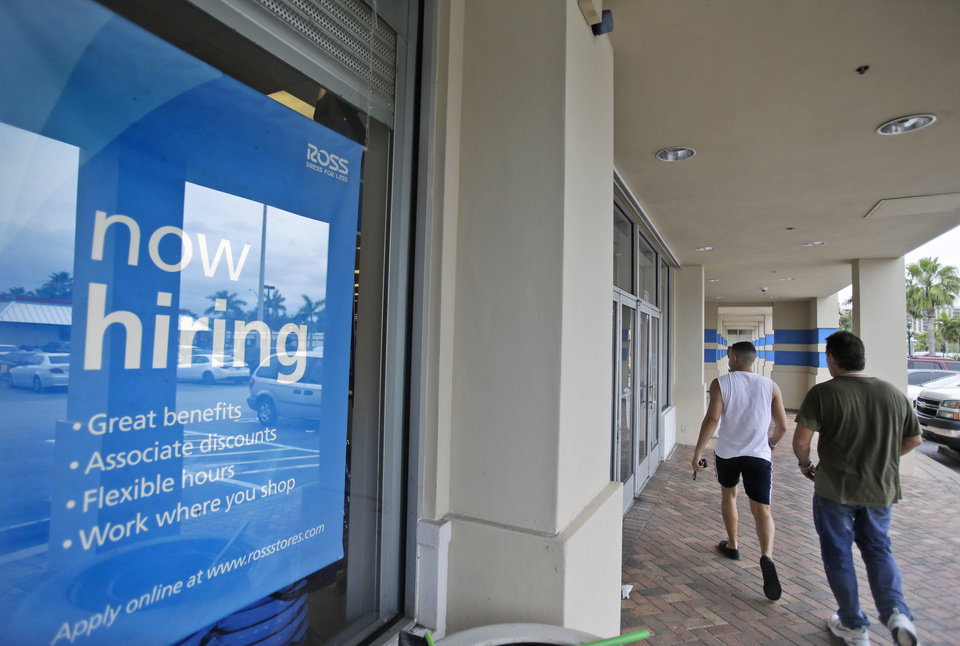 Photo - FILE - In this May 16, 2014 file photo, shoppers walk past a now hiring sign at a Ross store in North Miami Beach, Fla. As the economic recovery enters its sixth year, many Americans don't feel better off. (AP Photo/Wilfredo Lee, File)