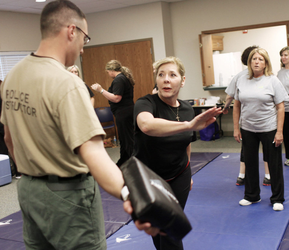 Photo - Edmond employee Linda Courtright practices punches with instructor Ben Daves.