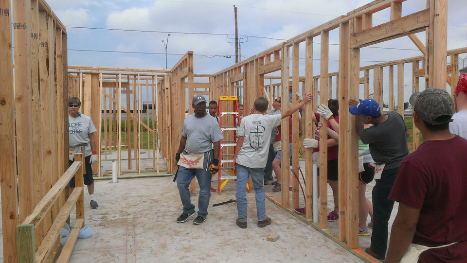 Photo -  Members of Shartel Church of God who participated in the Lose to Serve fitness challenge, along with Lose to Serve and Habitat for Humanity experts, work on the frame for Karissa Smith's new home. Photo provided