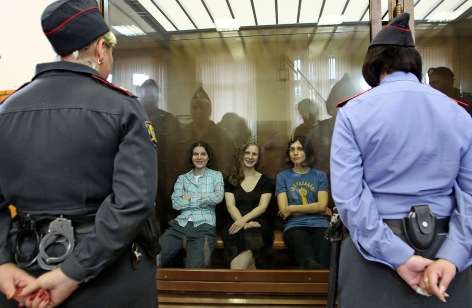 Photo -   Feminist punk group Pussy Riot members, from left, Yekaterina Samutsevich, Maria Alekhina and Nadezhda Tolokonnikova sit in a glass cage at a court room in Moscow, Russia on Friday, Aug 17, 2012. The women, two of whom have young children, are charged with hooliganism connected to religious hatred but the case is widely seen as a warning that authorities will only tolerate opposition under tightly controlled conditions. T-shirt on right worn by Tolokonnikova is Spanish and translates to