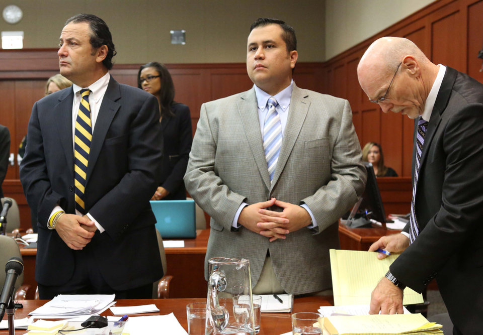 Photo - George Zimmerman, center, with jury consultant Robert Hirschhorn, left, and co-counsel Don West, stands for the arrival of a prospective juror in Seminole circuit court during Zimmerman's trial, in Sanford, Fla., Wednesday, June 12, 2013. Zimmerman has been charged with second-degree murder for the 2012 shooting death of Trayvon Martin.(AP Photo/Orlando Sentinel, Joe Burbank, Pool)