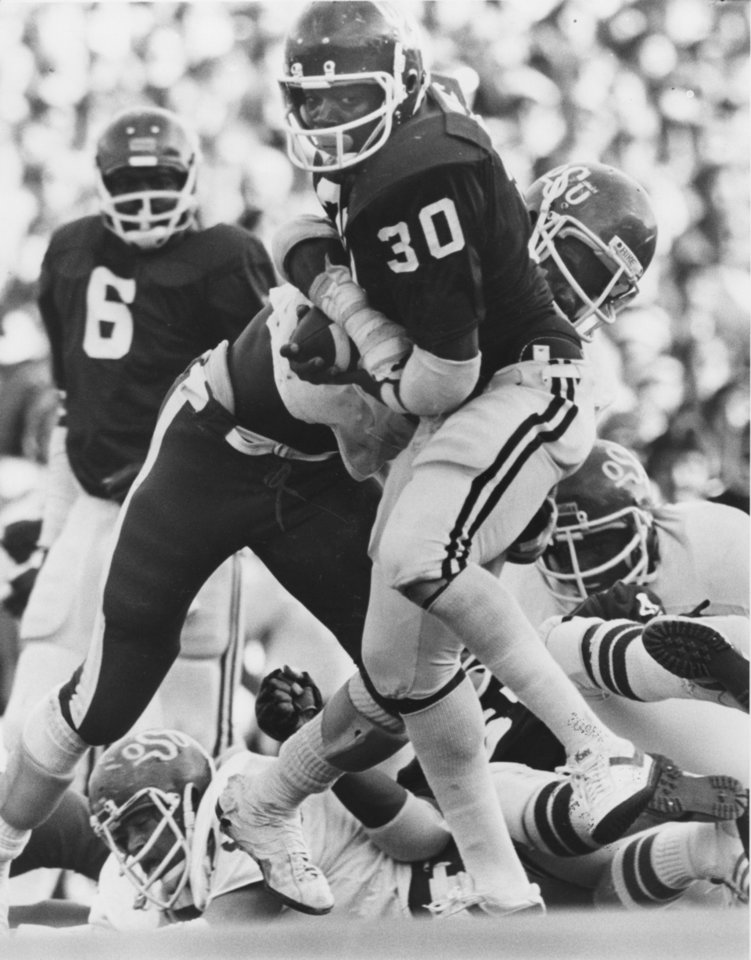 Oklahoma's Thomas Lott, back, watches teammate Kenny King run with the ball after giving him a handoff during a 1978 victory over Oklahoma State.' Photo taken by Doug Hoke. Photo taken 11-18-1978.   <strong>Dough Hoke -  Staff Photo </strong>