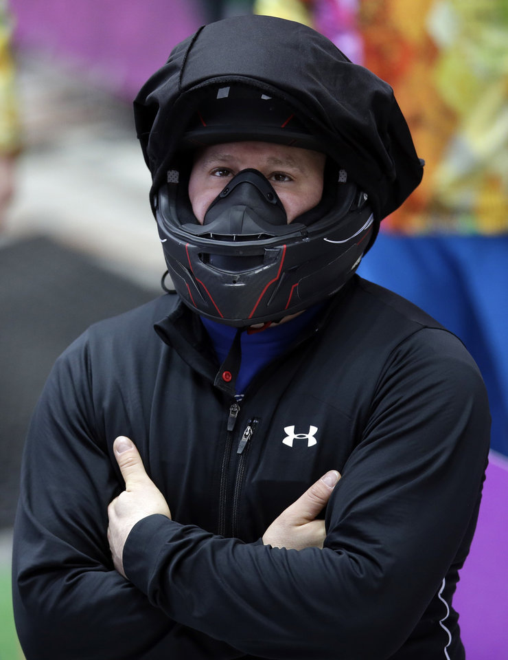 Photo - The driver of USA-1, Steven Holcomb, prepares for the start of his run during the men's four-man bobsled training at the 2014 Winter Olympics, Thursday, Feb. 20, 2014, in Krasnaya Polyana, Russia. (AP Photo/Michael Sohn)