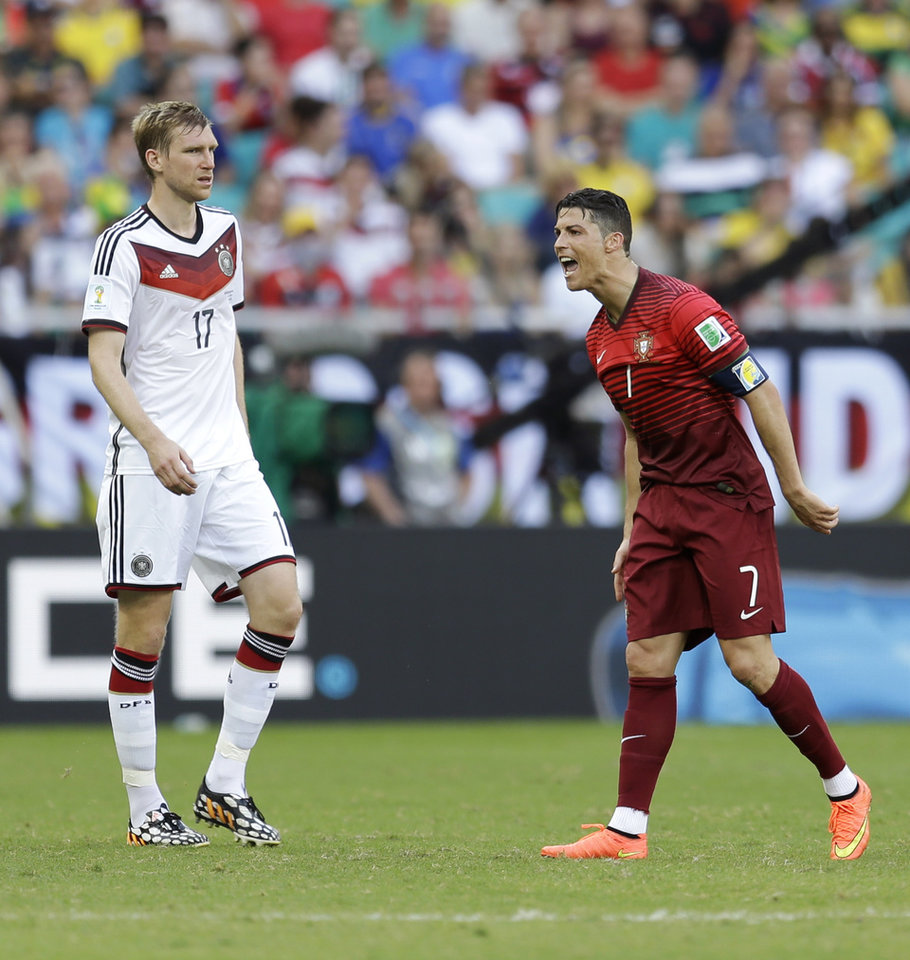 Photo - Portugal's Cristiano Ronaldo, right, yells at his teammates as Germany's Per Mertesacker watches during the group G World Cup soccer match between Germany and Portugal at the Arena Fonte Nova in Salvador, Brazil, Monday, June 16, 2014.  (AP Photo/Natacha Pisarenko)