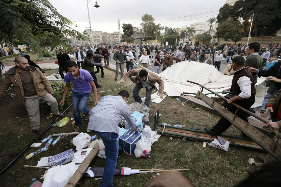 Photo - Supporters of Egyptian President Mohammed Morsi remove tents of opposition protesters outside the presidential palace, in Cairo, Egypt, Wednesday, Dec. 5, 2012. Supporters of Morsi and opponents clashed outside the presidential palace. Wednesday's clashes began when thousands of Islamist supporters of Morsi descended on the area around the palace where some 300 of his opponents were staging a sit-in. (AP Photo/Hassan Ammar)