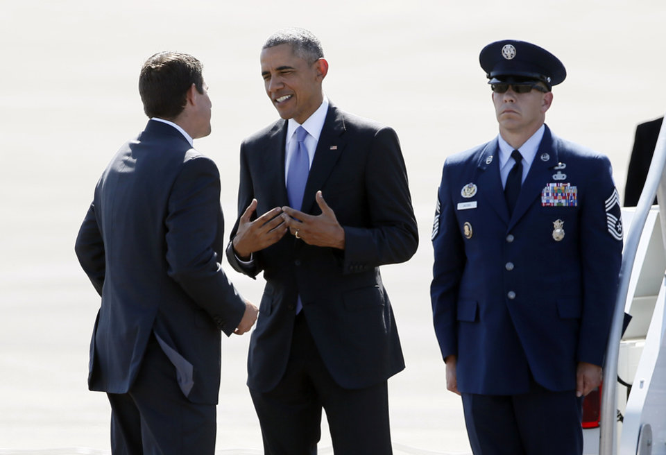 Photo - Denison Mayor Jared Johnson, left, talks with President Barack Obama after the President's arrival at the North Texas Regional Airport in Denison, Texas, Wednesday, July 15, 2015. (AP Photo/Tony Gutierrez)