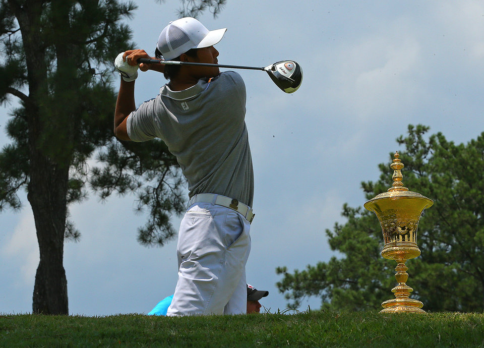 Photo - The trophy sits on the tee box as Gunn Yang tees off on the first hole during the 2014 U.S. Amateur Championship at Atlanta Athletic Club on Sunday, Aug. 17, 2014, in Johns Creek, Ga. (AP Photo/Atlanta Journal-Constitution, Curtis Compton)  MARIETTA DAILY OUT; GWINNETT DAILY POST OUT; LOCAL TV OUT; WXIA-TV OUT; WGCL-TV OUT