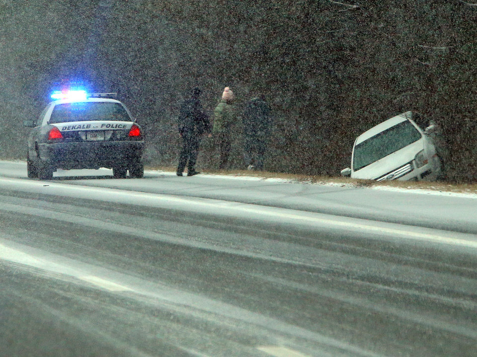 Photo - A Dekalb Police officer stops to check on Jesse Hatcher after he says another motorist caused him to lose control of his car and spin into the ditch off I-20 West near Conyers on Tuesday, Jan. 28, 2014, in Conyers.  (AP Photo/Atlanta Journal-Constitution, Curtis Compton)