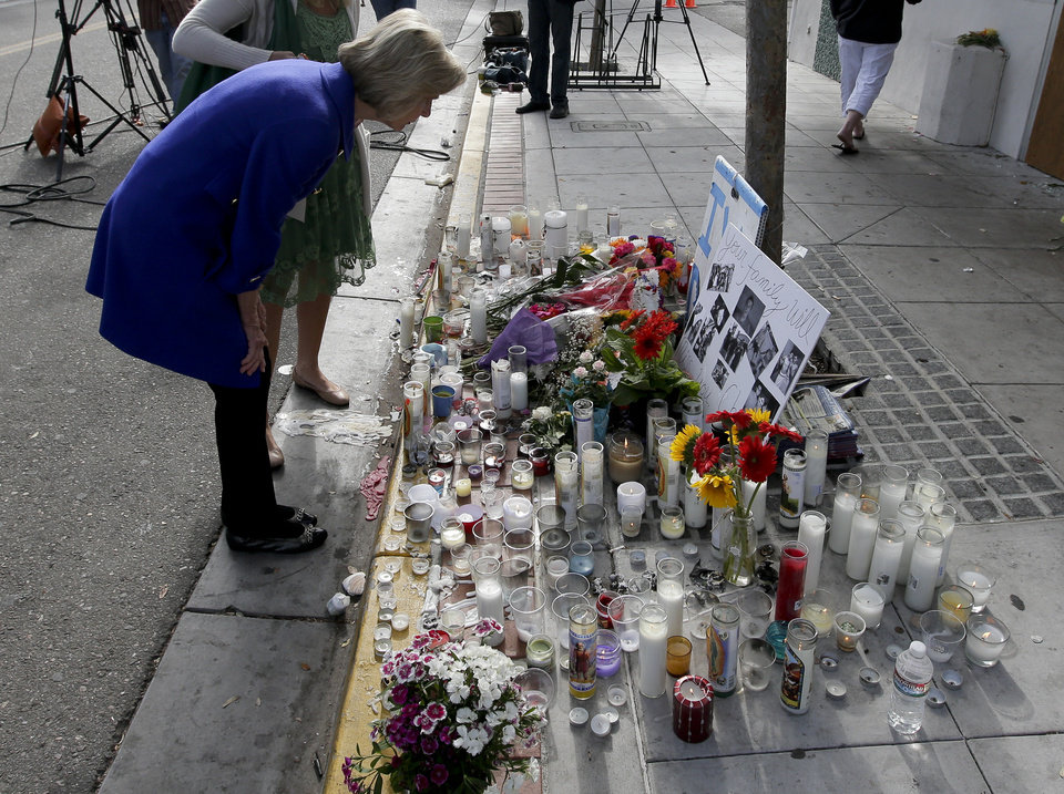 Photo - Rep. Lois Capps, D-Santa Barbara, pays her respects at a makeshift memorial in front of the IV Deli Mart, where part of Friday night's mass shooting took place by a drive-by shooter Sunday, May 25, 2014 in the Isla Vista area near Goleta, Calif. Calif. Sheriff's officials said Elliot Rodger, 22, went on a rampage near the University of California, Santa Barbara, stabbing three people to death at his apartment before shooting and killing three more in a crime spree through a nearby neighborhood. (AP Photo/Chris Carlson)
