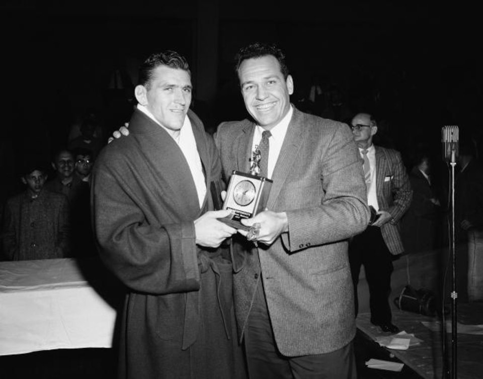 Photo -  Danny Hodge, left, receives the Outstanding Wrestling Award from Ray Jenkins, president of the American Wrestling Coaches Association, on March 31, 1957, in Pittsburgh. It was the second straight year Hodge won the award, and the third time the Sooner claimed the 177-pound crown. [AP Photo/Walter Stein]