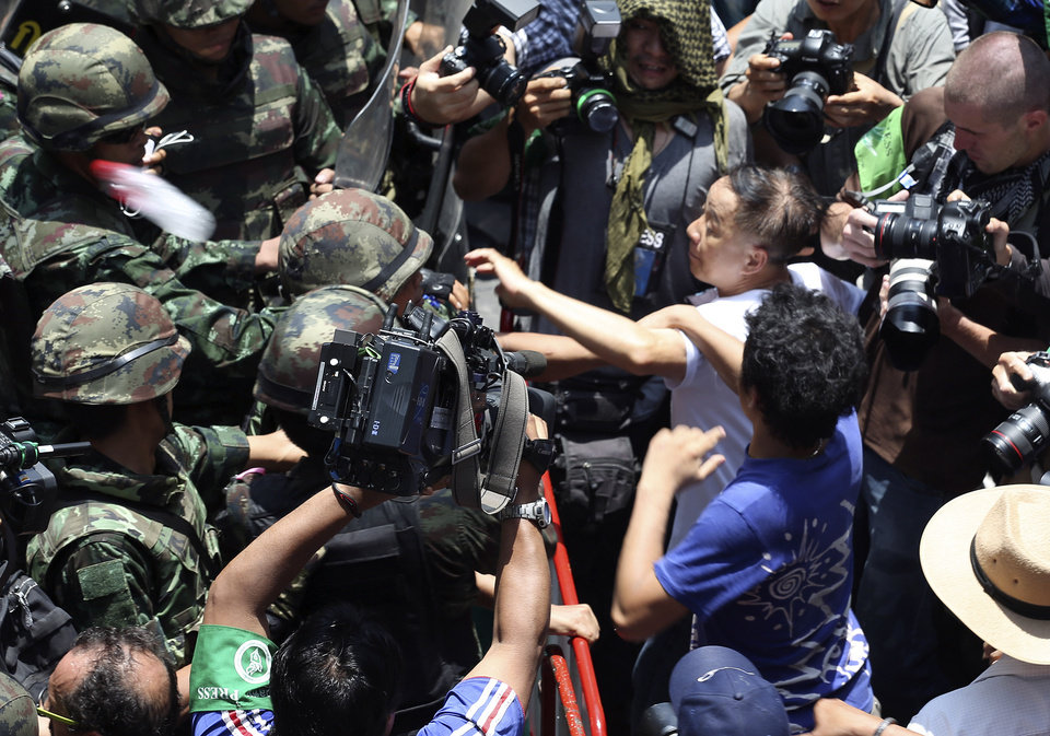 Photo - Protesters, right, scuffle with Thai soldiers during an anti-coup demonstration outside a shopping mall in Bangkok, Thailand Sunday, May 25, 2014. A spokesman for Thailand's coup leaders said Sunday that democracy had caused