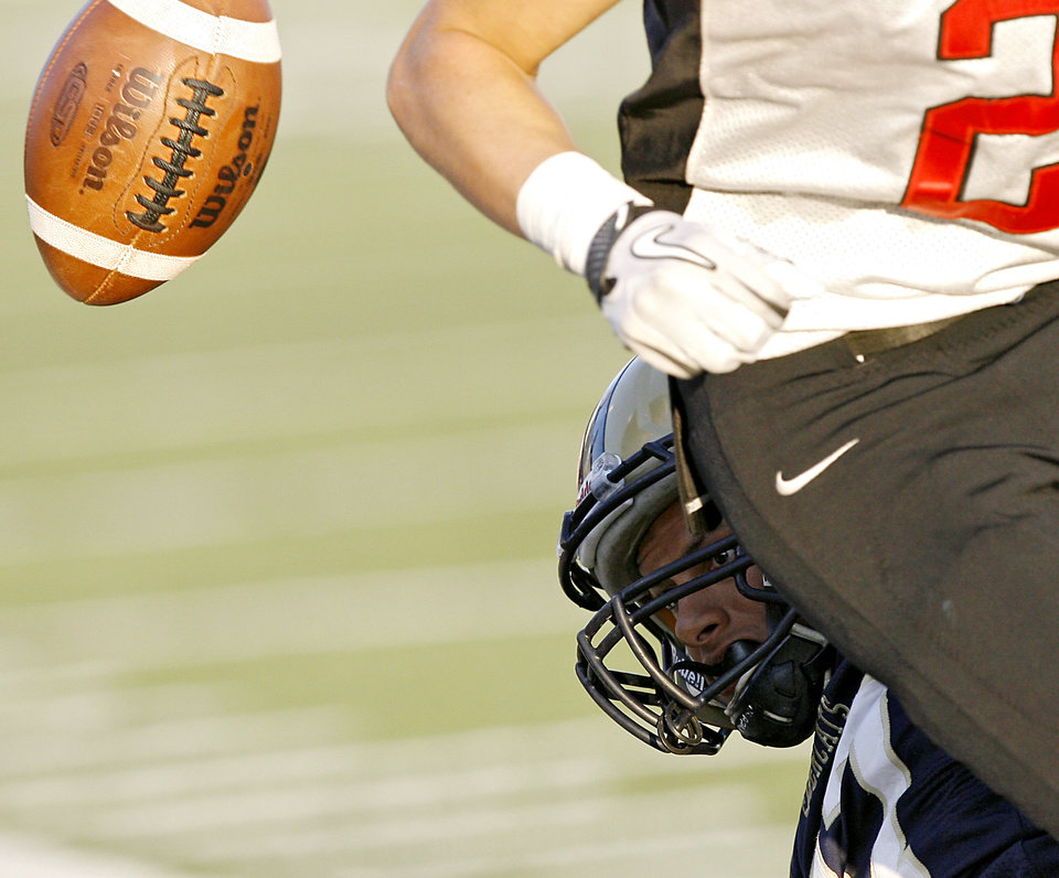 Photo - Southmoore's Spencer Martin keeps his eye on a loose ball as he tackles Westmoore's Austin Bowling out of bounds during their high school football game at Moore Stadium in Moore, Oklahoma on Friday, September 9, 2011. Photo by John Clanton, The Oklahoman