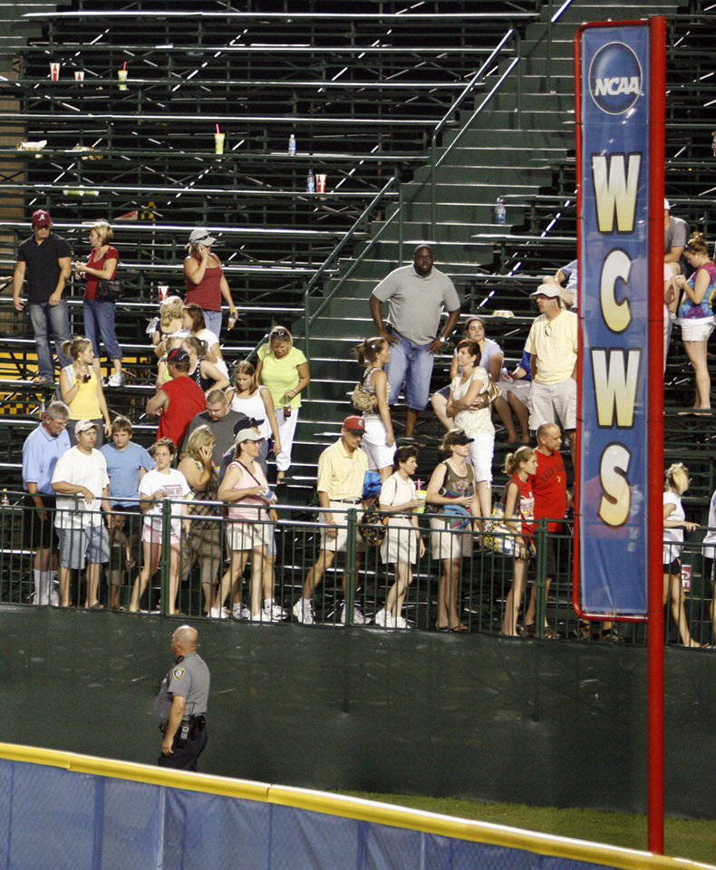 Photo - Fans file out of the stands due to a lightning delay in the sixth inning during the softball game in the Women's College World Series between Louisiana-Lafayette and Alabama at ASA Hall of Fame Stadium in Oklahoma City, Saturday, May 31, 2008. When the game resumed after midnight Alabama won, 3-1. BY NATE BILLINGS, THE OKLAHOMAN