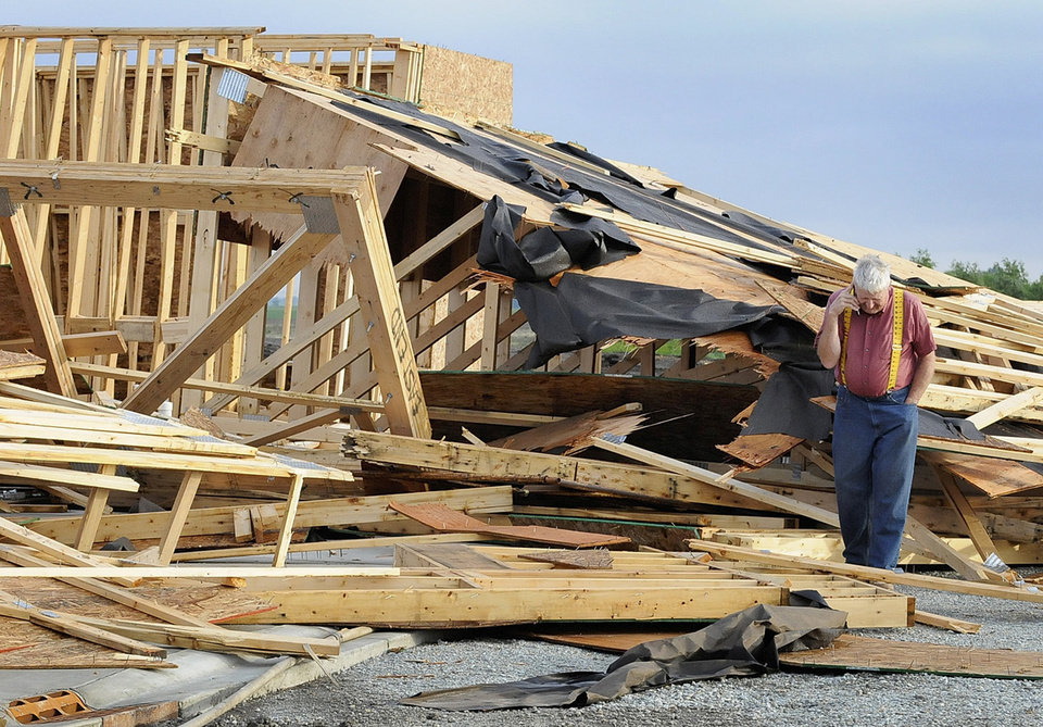 Photo - Tim Brettin of the Laborers for Christ surveys what remains of the Risen Savior Lutheran Church he has been helping to build in Manteno, Ill., after thunderstorms punched through northern Illinois overnight causing significant wind damage, mainly in rural areas west and south of Chicago. Brettin and his wife, Peg, were in their recreational vehicle parked next to the church Wednesday evening when high winds destroyed the building. (AP Photo/The Daily Journal, Mike Voss)