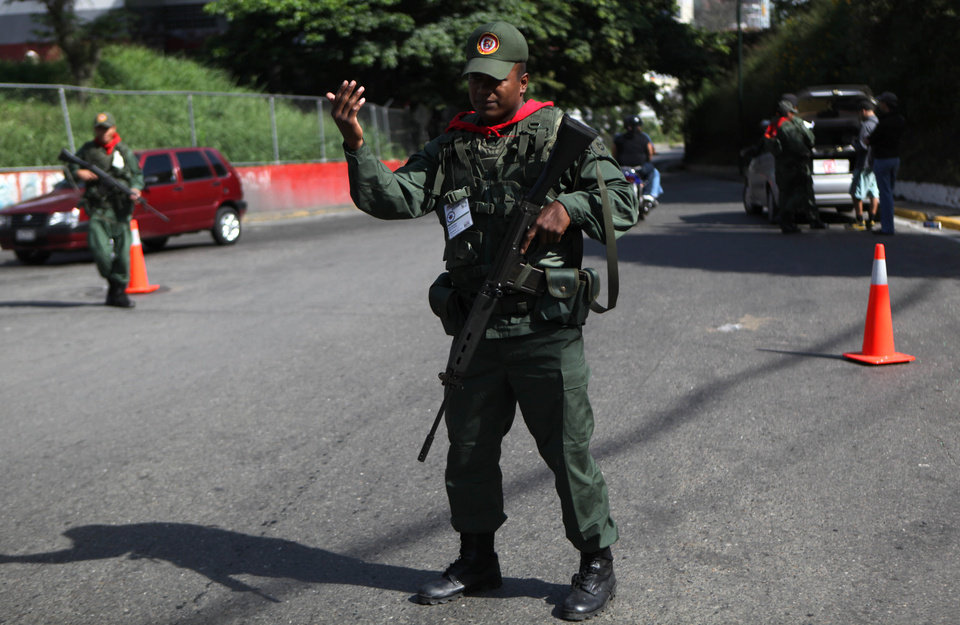 Members of the Bolivarian militia, a militia created by President Hugo Chavez estimated to number more than 100,000 who do not report to the armed forces, stand at a checkpoint in the 23 de Enero neighborhood of Caracas, Venezuela, Saturday, Oct. 6, 2012. Chavez is running for re-election against opposition candidate Henrique Capriles in Sunday's presidential election. (AP Photo/Rodrigo Abd)