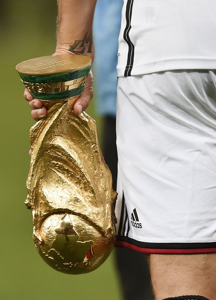 Photo - Germany's Toni Kroos walks with the trophy after the World Cup final soccer match between Germany and Argentina at the Maracana Stadium in Rio de Janeiro, Brazil, Sunday, July 13, 2014. Germany won the match 1-0. (AP Photo/Martin Meissner)