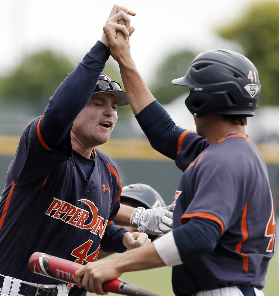 Photo - Pepperdine's Brandon Caruso (41) is congratulated by teammate Connor Garelick (44) after scoring a run on an RBI by teammate Aaron Brown, not pictured, during the first inning of an NCAA college baseball tournament super regional game against the TCU in Fort Worth, Texas, Monday, June 9, 2014. (AP Photo/Brandon Wade)