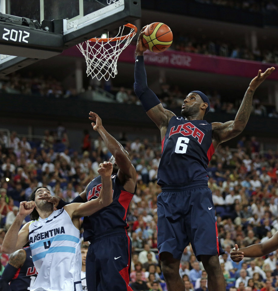 Photo -   United States' LeBron James, right, grabs a rebound as teammate Kobe Bryant blocks out Argentina's Luis Scola during a men's semifinals basketball game at the 2012 Summer Olympics, Friday, Aug. 10, 2012, in London. (AP Photo/Charles Krupa)