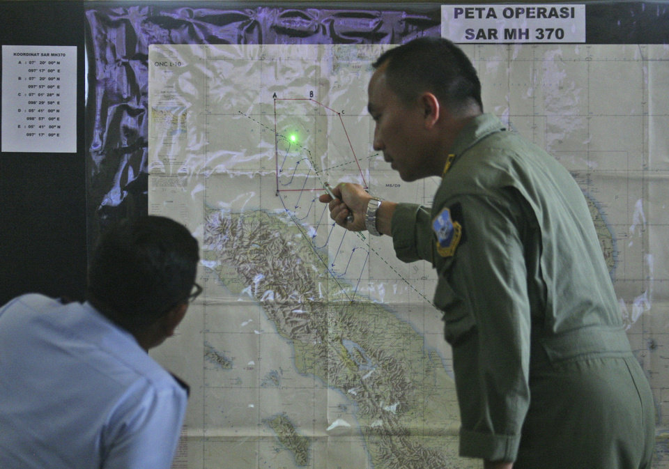 Photo - Indonesian Air Force officers examine a map of the Malacca Strait during a briefing following a search operation for the missing Malaysia Airlines Boeing 777, at Suwondo air base in Medan, North Sumatra, Indonesia, Wednesday, March 12, 2014. Malaysia asked India to join the expanding search for the missing jetliner near the Andaman Sea,  far to the northwest of its last reported position and a further sign Wednesday that authorities have no idea where the plane might be more than four days after it vanished. (AP Photo/Binsar Bakkara)