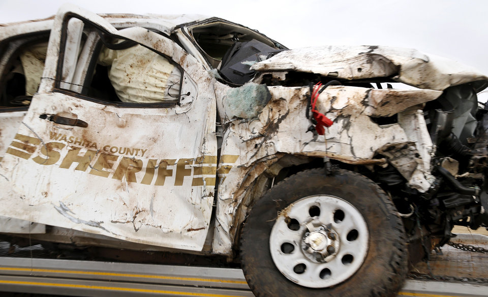 Photo - The Washita County Sheriff's Department SUV driven by Undersheriff Brian Beck, 39, is removed from the crash scene where Beck was killed. A Burns Flat police officer and an undersheriff for the Washita County Sheriff's Department died in a car crash on Thursday, Jan. 23, 2014, at a rural intersection about one mile south of Dill City.  According to OHP spokesman, the lawmen became involved in a high-speed pursuit  when a Washita County man fled as the undersheriff approached him to serve a felony warrant Thursday morning.  That same suspect died about the same time in another crash about three miles east of the location where the law officers collided. Dill City is located 75 miles west of Oklahoma City. Photo by Jim Beckel, The Oklahoman