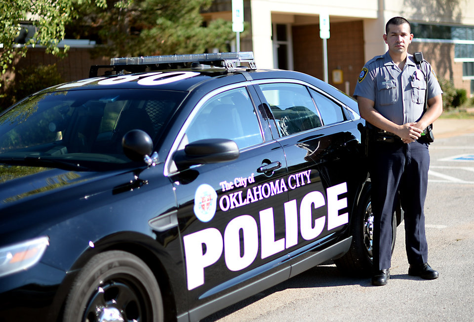 Photo -  Oklahoma City police officer Allan Cruz poses in front of the Springlake Division in Oklahoma City. [Photo by Jackie Dobson, For The Oklahoman]