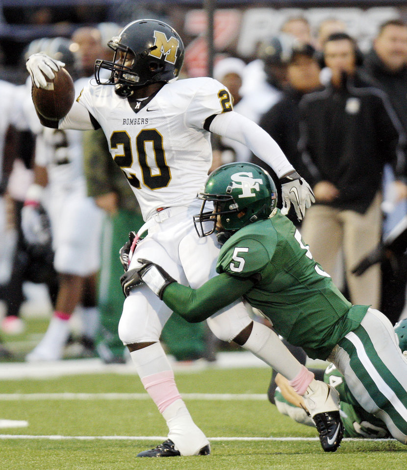 Edmond Santa Fe's Khari Harding (5) tries to bring down James Flanders (20) of Midwest City during a high school football game between Midwest City and Edmond Santa Fe at Wantland Stadium in Edmond, Okla., Thursday, Sept. 15, 2011. Photo by Nate Billings, The Oklahoman