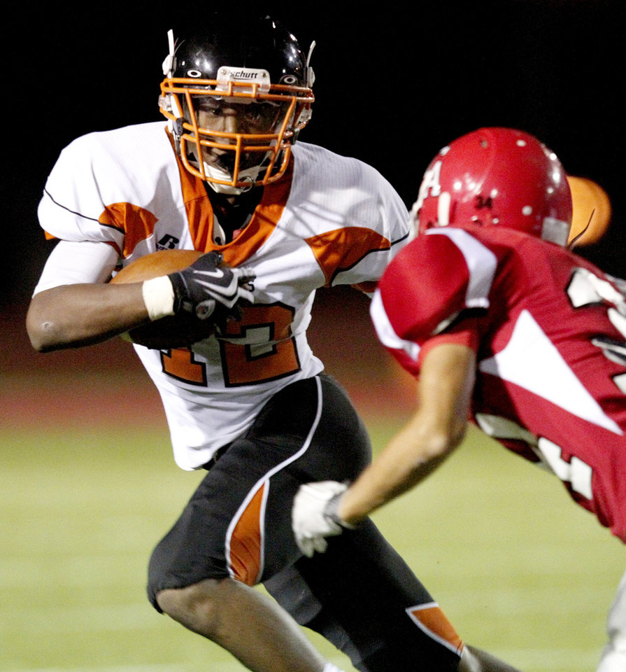 Photo - Tyler Lockett of Booker T. Washington tries to get by Carl Albert's Justin Love during a high school football game in Midwest City, Okla., Friday, September 3, 2010.  Photo by Bryan Terry, The Oklahoman