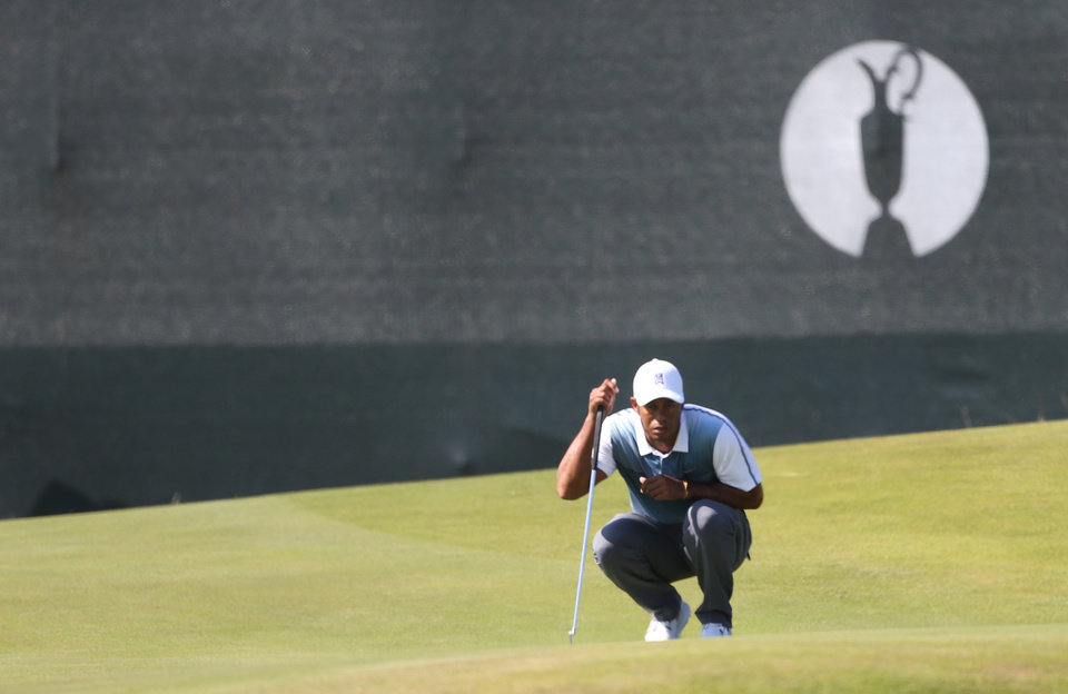 Photo - Tiger Woods of the US prepares to putt on the 4th green during the first day of the British Open Golf championship at the Royal Liverpool golf club, Hoylake, England, Thursday July 17, 2014. (AP Photo/Peter Morrison)