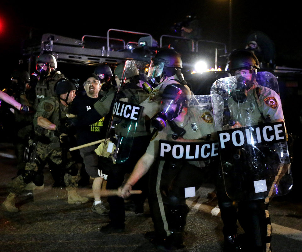 Photo - A man is detained after a standoff between protesters and police Monday, Aug. 18, 2014, during a protest for Michael Brown, who was killed by a police officer Aug. 9 in Ferguson, Mo. Brown's shooting has sparked more than a week of protests, riots and looting in the St. Louis suburb. (AP Photo/Charlie Riedel)