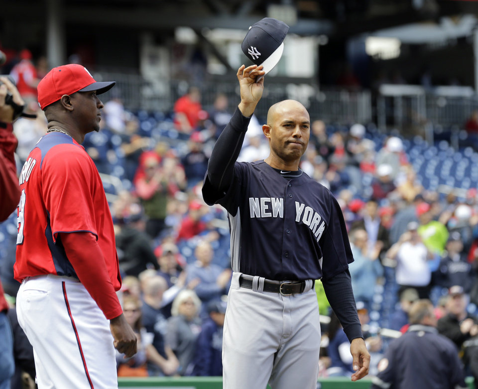 Photo - New York Yankees relief pitcher Mariano Rivera, center raises his cap during a presentation before an exhibition baseball game at Nationals Park on Friday, March 29, 2013, in Washington. Washington Nationals relief pitcher Rafael Soriano is at left, (AP Photo/Alex Brandon)