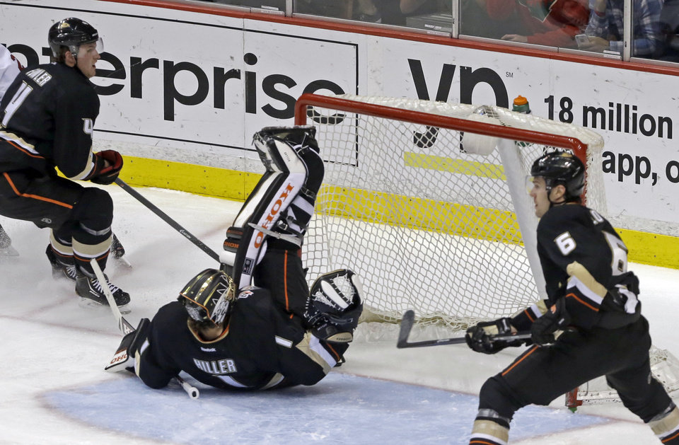 Photo - Anaheim Ducks goalie Jonas Hiller (1), of Switzerland, is upended blocking a Minnesota Wild shot in the second period of an NHL hockey game in Anaheim, Calif., Tuesday, Jan. 28, 2014. (AP Photo/Reed Saxon)