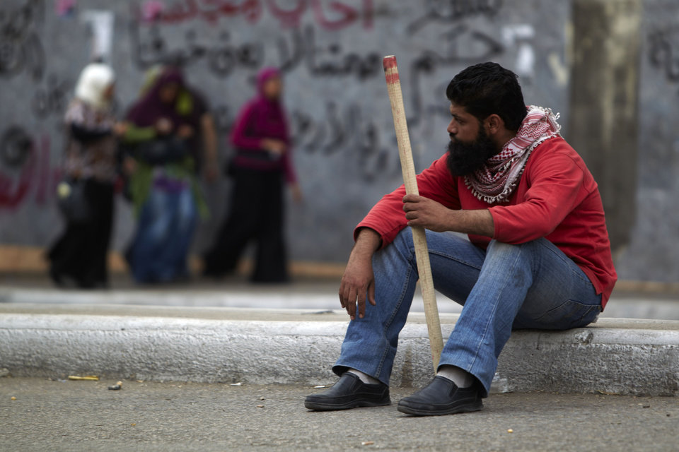 Photo -   In this Monday, April 30, 2012 photo, a protester sitting on a sidewalk holds a stick in Cairo, Egypt. Security officials say a protester has been killed when clashes erupted between unidentified assailants and demonstrators gathered outside the Defense Ministry in the Egyptian capital to call for an end to military rule. (AP Photo/Fredrik Persson)