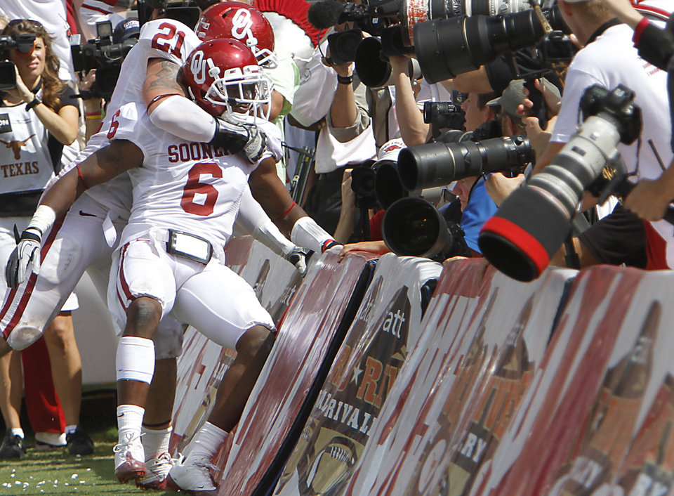 Photo - Oklahoma's Tom Wort (21) and Demontre Hurst (6) celebrate in front of the cameras after Hurst returned an interception for a touchdown during the Red River Rivalry college football game between the University of Oklahoma Sooners (OU) and the University of Texas Longhorns (UT) at the Cotton Bowl in Dallas, Saturday, Oct. 8, 2011. Photo by Chris Landsberger, The Oklahoman