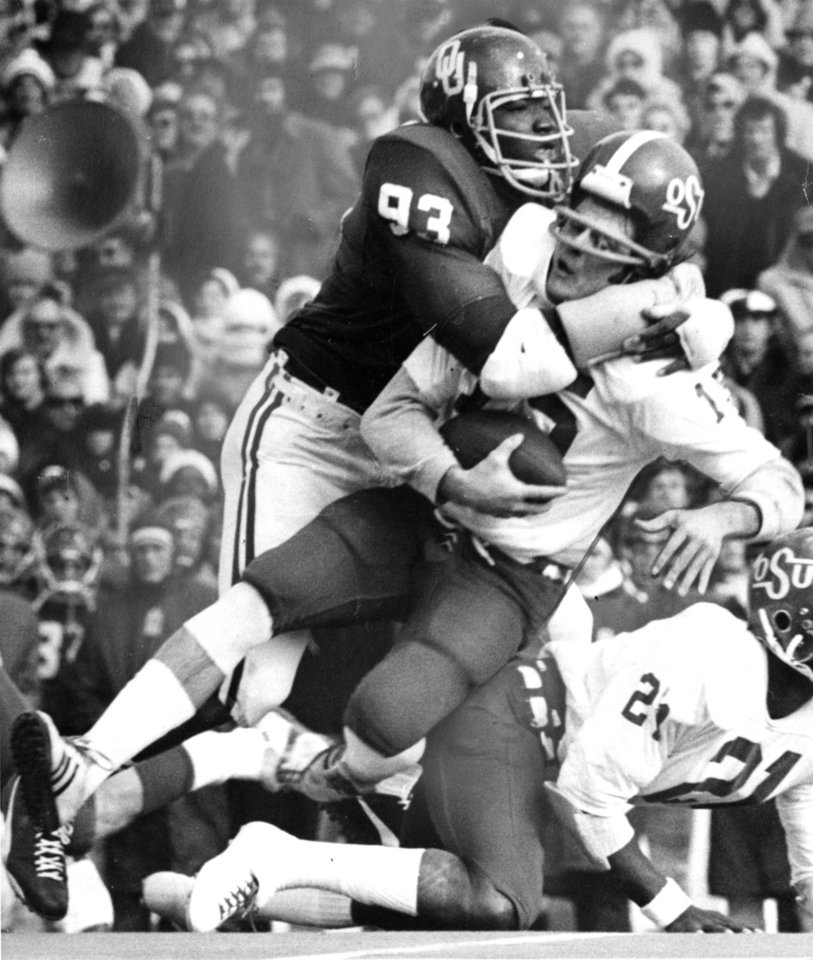 Photo - Cowboy quarterback Charlie Weatherbie is about to lose his helmet and his head may not be too secure after a smothering tackle by Lee Roy Selmon during the Bedlam college football game between OU and OU on Nov 30, 1974. OU won, 44-13. Staff photo by Bob Albright