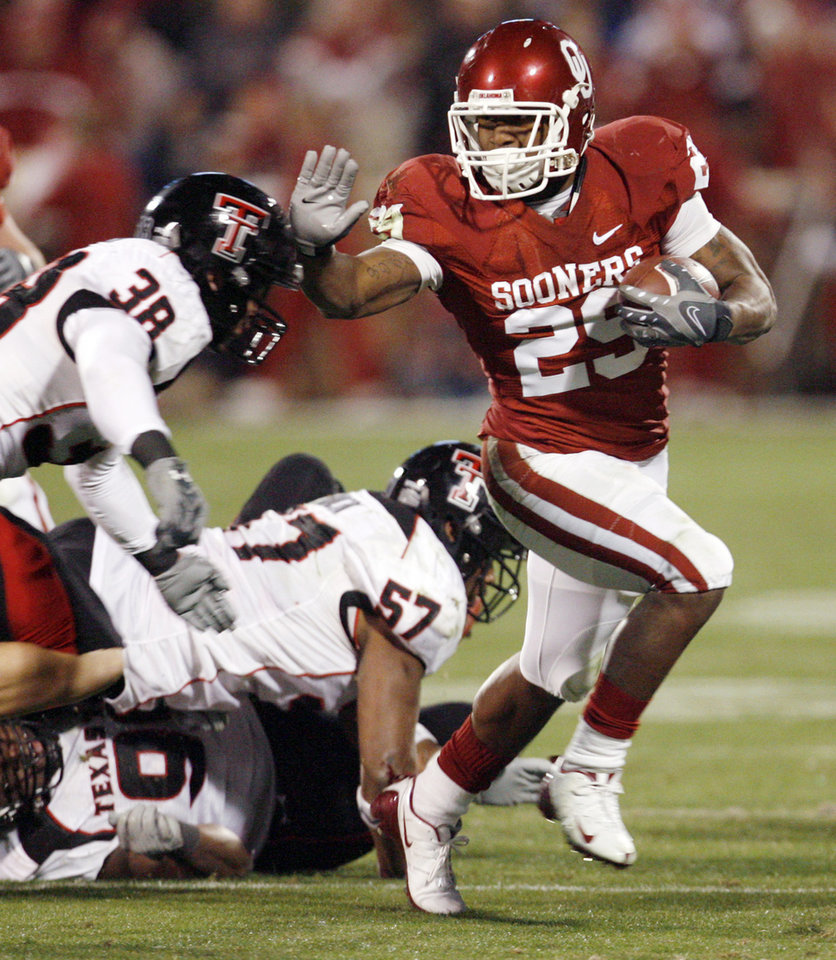 Photo - OU's Chris Brown (29) stiff arms Jordy Rowland (38) of Texas Tech on a run in the second half of the college football game between the University of Oklahoma Sooners and Texas Tech University at Gaylord Family -- Oklahoma Memorial Stadium in Norman, Okla., Saturday, Nov. 22, 2008. BY NATE BILLINGS, THE OKLAHOMAN