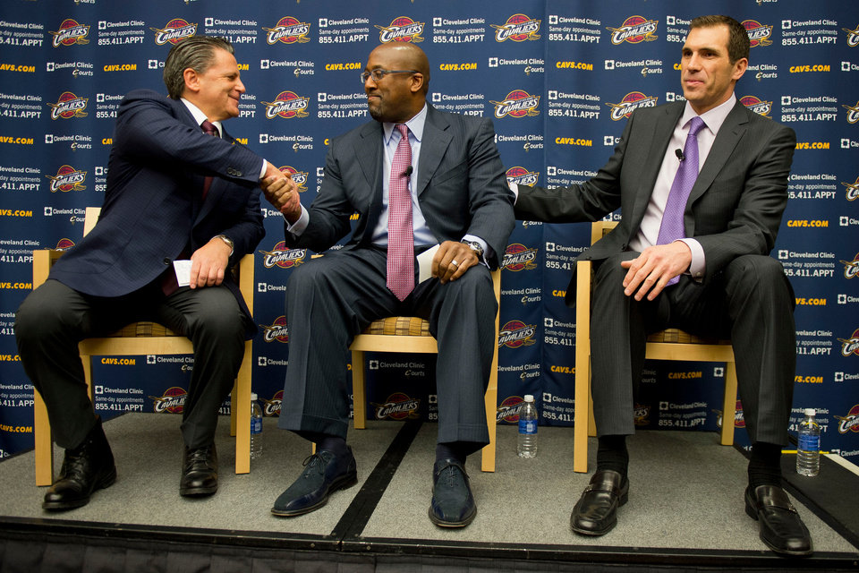 Photo - Cleveland majority owner Dan Gilbert, left, congratulates new head coach Mike Brown with general manager Chris Grant, right, during a press conference at the team's headquarters to introducing Brown on Wednesday, April 24, 2013, in Independence, Ohio. (AP Photo/Jason Miller)
