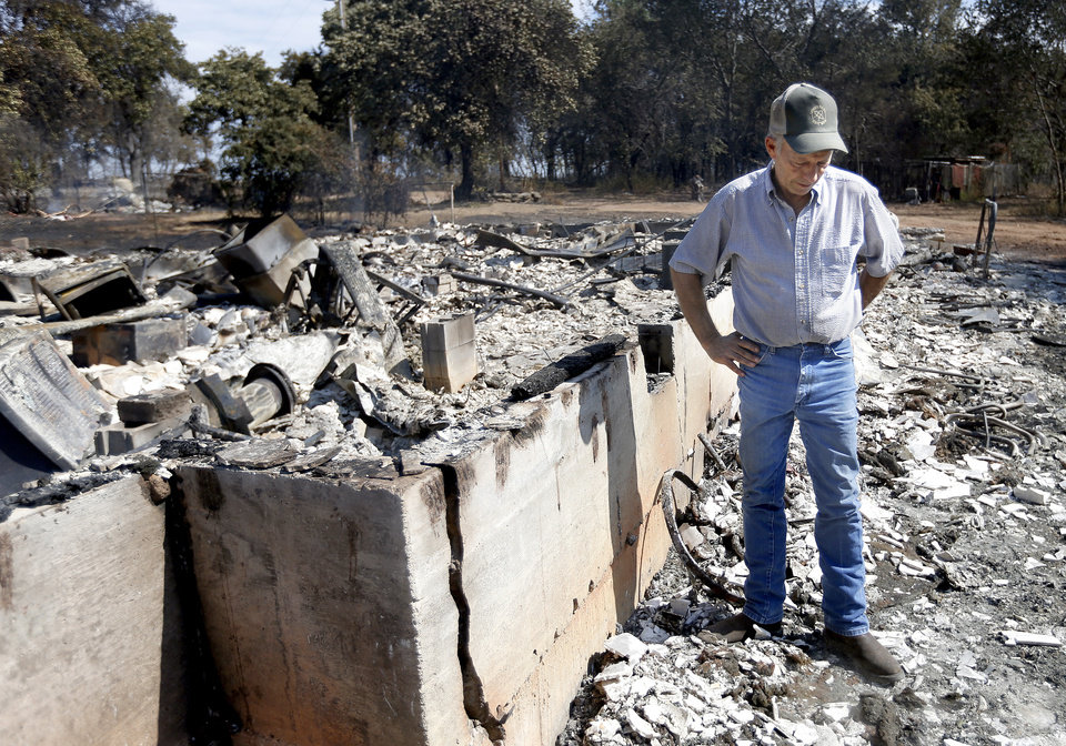 Photo - Doug Roberson looks over damage at the home of Oscar Montelongo, Sunday, Aug. 5, 2012, in Glencoe, Okla., after wildfires moved through the area Saturday.