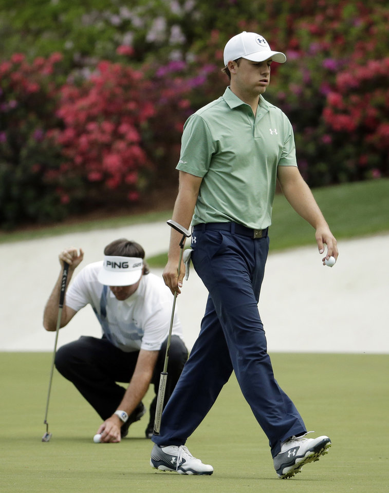 Photo - Bubba Watson, left, lines up his putt as Jordan Spieth walks off the 13th green during the fourth round of the Masters golf tournament Sunday, April 13, 2014, in Augusta, Ga. (AP Photo/Chris Carlson)