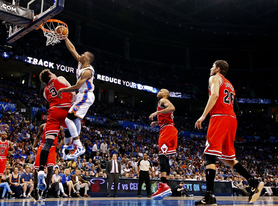 Photo - Oklahoma City's Russell Westbrook (0) dunks over Chicago's Omer Asik (3) during the NBA basketball game between the Chicago Bulls and the Oklahoma City Thunder at Chesapeake Energy Arena in Oklahoma City, Sunday, April 1, 2012. Photo by Sarah Phipps, The Oklahoman