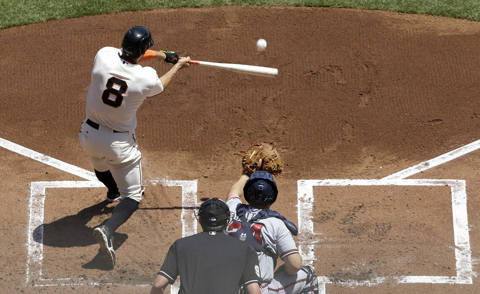 Photo - San Francisco Giants' Hunter Pence (8) hits a two-run home run off of Atlanta Braves pitcher Julio Teheran in front of catcher Evan Gattis during the first inning of a baseball game in San Francisco, Wednesday, May 14, 2014. (AP Photo)