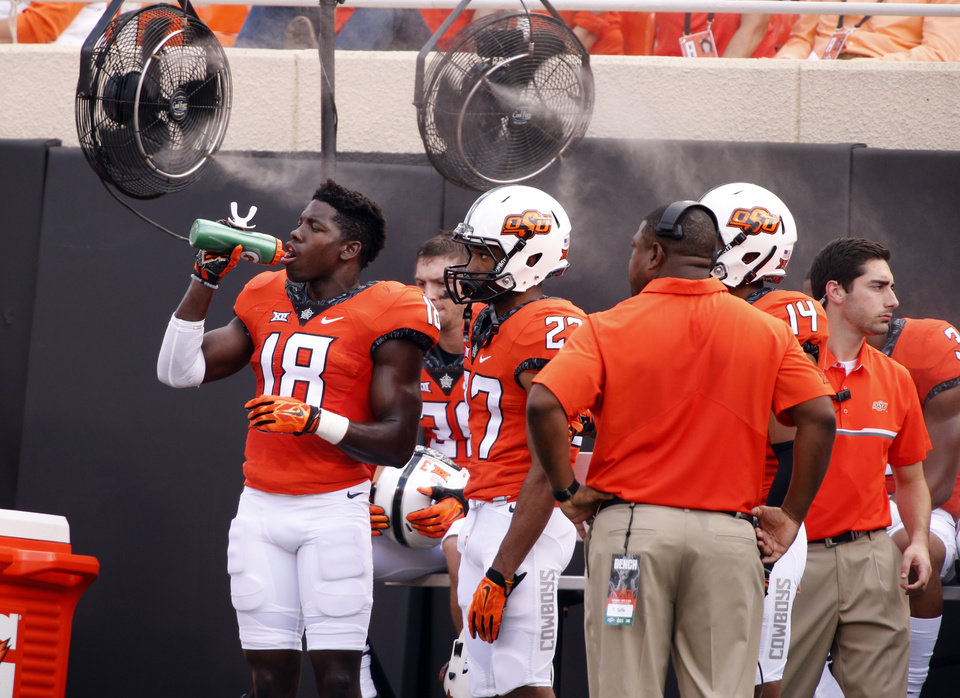 Photo - Oklahoma State's Za'Carrius Green (18) gets a drink on the sidelines with cooling misters in the background during the college football game between the Oklahoma State Cowboys (OSU) and the Southeastern Louisiana Lions at Boone Pickens Stadium in Stillwater, Okla., Saturday, Sept. 12, 2015. Photo by Steve Sisney, The Oklahoman