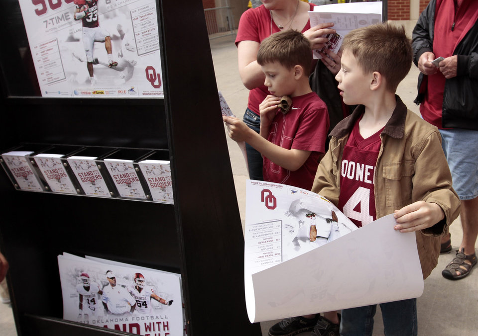 Photo - Twins Brighton and Peyton Combs, 8, from Owasso, collect free posters and schedules before the annual Spring Football Game at Gaylord Family-Oklahoma Memorial Stadium in Norman, Okla., on Saturday, April 13, 2013. Photo by Steve Sisney, The Oklahoman