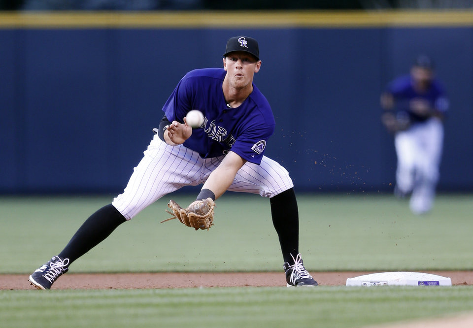 Photo - Colorado Rockies second baseman DJ LeMahieu catches a bad throw from catcher Wilin Rosario allowing Washington Nationals' Anthony Rendon to steal second during the first inning of a baseball game on Monday, July 21, 2014, in Denver. (AP Photo/Jack Dempsey)