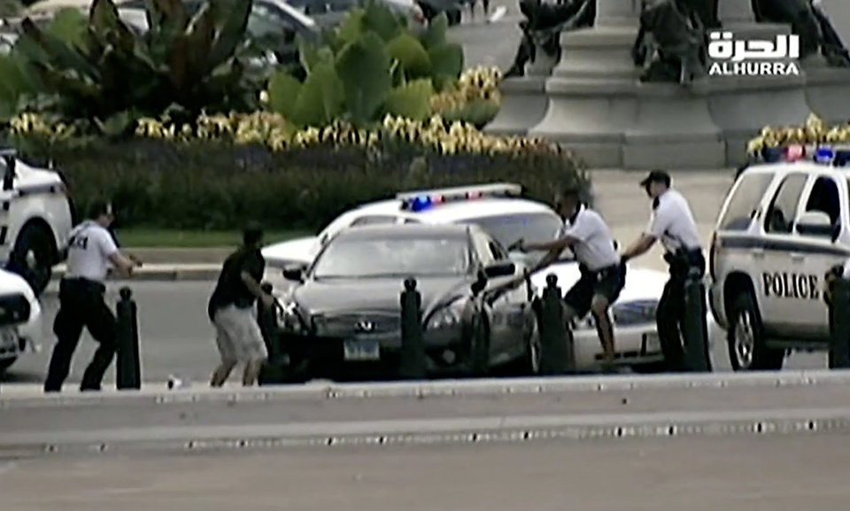 Photo - This image from video provided by Alhurra Television shows police with guns drawn surrounding a black Infiniti near the U.S. Capitol in Washington, Thursday, Oct. 3, 2013. A woman with a young child inside tried to ram through a White House barricade, then led police on a chase toward the Capitol, where police shot and killed her, witnesses and officials said. (AP Photo/Alhurra Television)